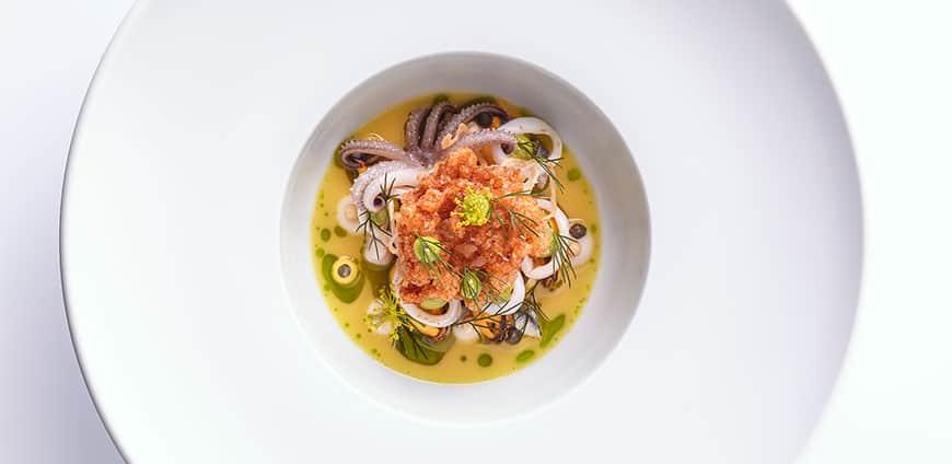 aqua-muscheln-calamaretti-safran-curry-fond-anchovis-zwiebelcreme-gebackenes-ruehrei-kapern-dill-pinienkerne-credit-goetz-wrage-1-slider