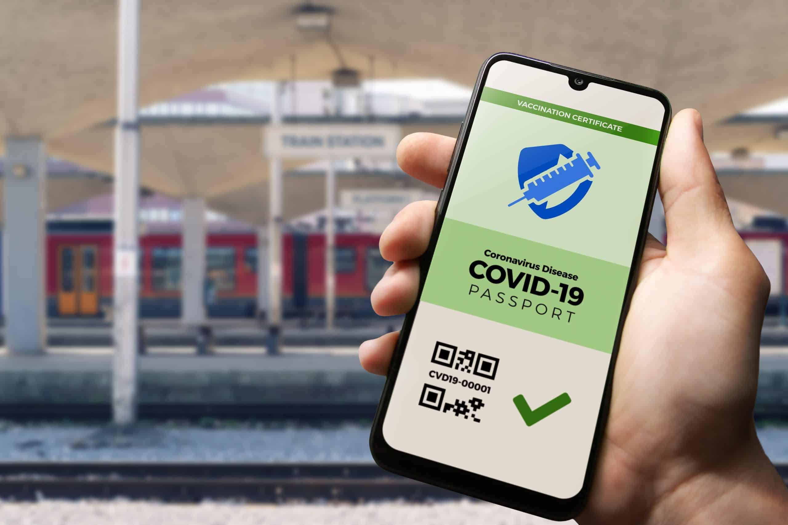 Hand hält Smartphone mit Grünem Pass vor Bahnsteig